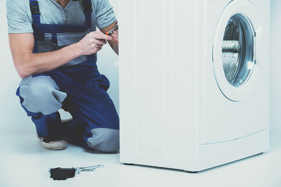 professional appliance repairman doing washer repair